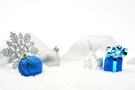 blue sphere: Decoration of silver and blue glitter baubles with ribbon and snowflake on snow on white background