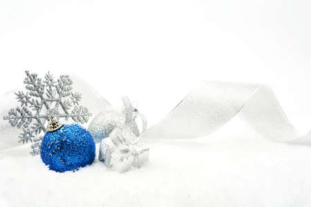 christmas motif: Decoration of silver and blue glitter baubles with ribbon and snowflake on snow on white background