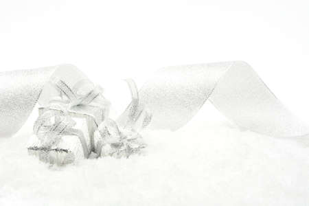 gewgaw: Decoration of silver christmas gifts with ribbon on snow on white background Stock Photo