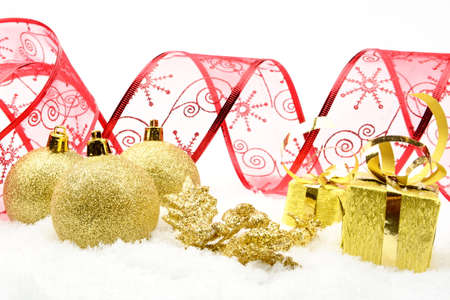 Decoration of golden christmas gifts,baubles,red ribbon on snow withon white photo