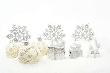 Decoration of silver christmas gifts,baubles,ribbon on snow withon white photo