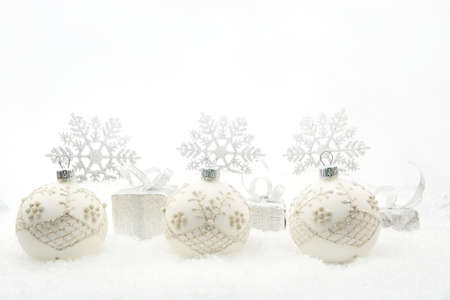 christmas motif: Decoration of silver christmas gifts and baubles and snowflakes on snow on white background