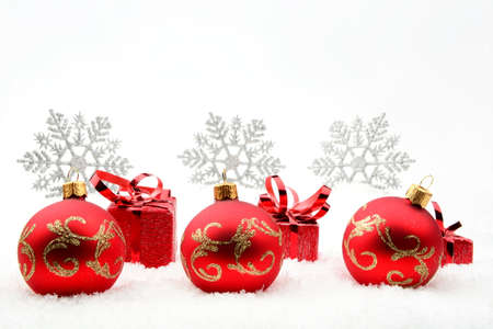 gewgaw: Decoration of red christmas gifts and baubles and snowflakes on snow on white background Stock Photo