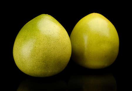 singular: Whole two pomelos, chinese grapefruits isolated on black background