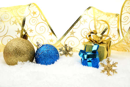 gewgaw: Decoration of golden and blue christmas baubles and gifts with ribbon on snow white background