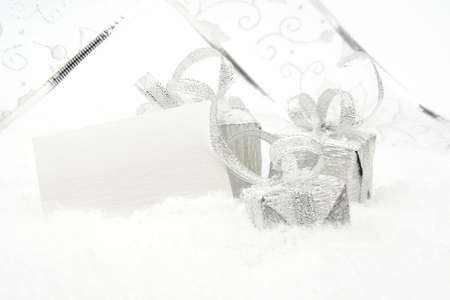gewgaw: Silver christmas decoration, gifts with ribbon with wishes card on snow white background Stock Photo