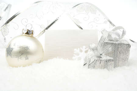 gewgaw: Decoration of silver christmas baubles and gifts with ribbon with wishes card on snow white background