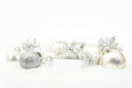 gewgaw: Decoration of silver christmas baubles and gifts with wishes card on snow white background
