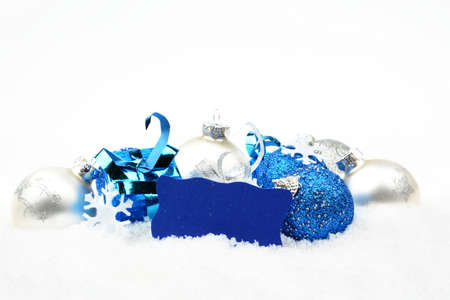 christmas motif: Decoration of silver and blue christmas baubles and gifts with wishes card on snow white background Stock Photo