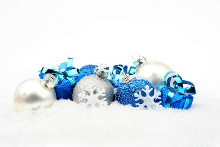 Decoration of blue,silver christmas baubles and gifts on snow white background