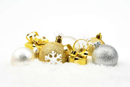 gewgaw: Decoration of golden,silver christmas baubles and gifts on snow white background Stock Photo