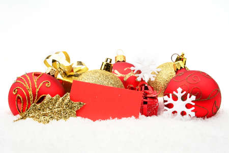 gewgaw: Decoration of golden,red christmas baubles and gifts with wishes card on snow isolated on white background