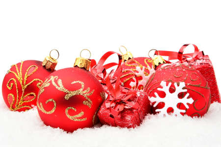 gewgaw: Decoration of red christmas baubles and gifts on snow white background
