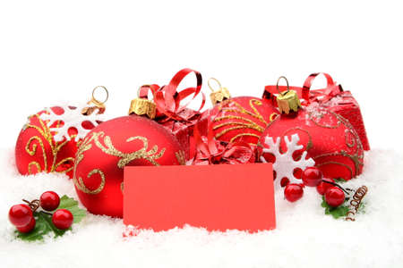 gewgaw: Decoration of red christmas baubles and gifts with wishes card on snow white background