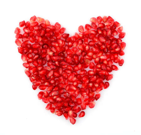 grenadine: Red heart made from seeds of pomegranate,grenadine on white background