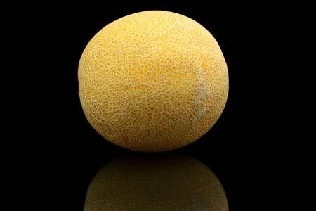 Studio shot of whole ripe melon called galia isolated on black background