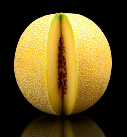 cancellated: Studio shot of notched ripe melon galia isolated on black background
