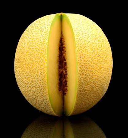 Studio shot of notched ripe melon galia isolated on black background