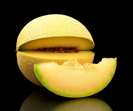 Studio shot of notched ripe melon galia with slice isolated on black background