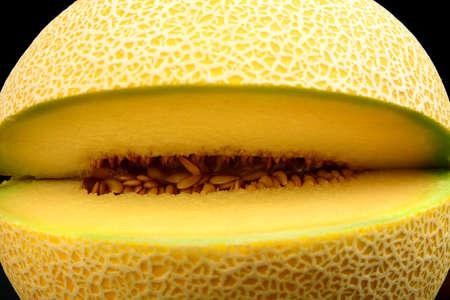Close-up shot of notched ripe melon galia isolated on black backgroun Stock Photo