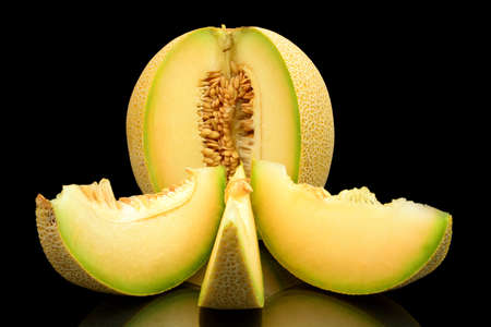 cancellous: Studio shot of notched ripe melon galia with slices isolated on black background Stock Photo
