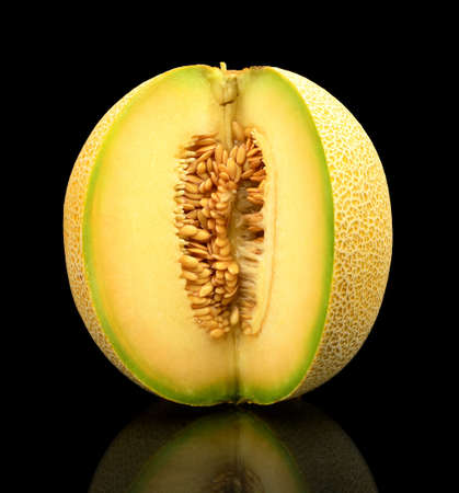 pip: Studio shot of notched ripe melon galia isolated on black background