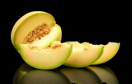 Studio shot of notched ripe melon galia with slices isolated on black background Stock Photo