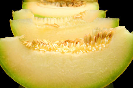 Studio shot of slices, pieces of melon galia isolated on black background