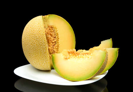 Studio shot of notched ripe melon galia with slices on plate isolated on black background