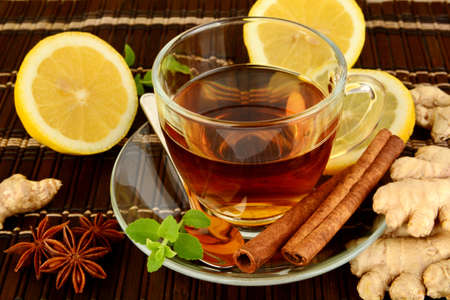 ginger tea: Ginger tea-ingwertee on brown mat with lemon,cinnamon,anise and mint on mat