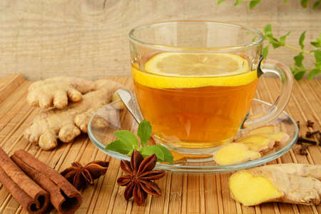 ginger tea: Ginger tea-ingwertee on wooden mat with lemon,cinnamon,anise and mint on mat Stock Photo
