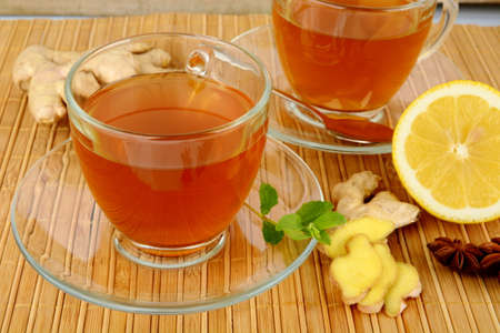 Ginger teas on wooden mat with lemon,anise and mint on mat Stock Photo