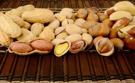 mat like: Many nuts like peanuts,walnuts,pistachios and brasil nuts, snacks in group on brown mat