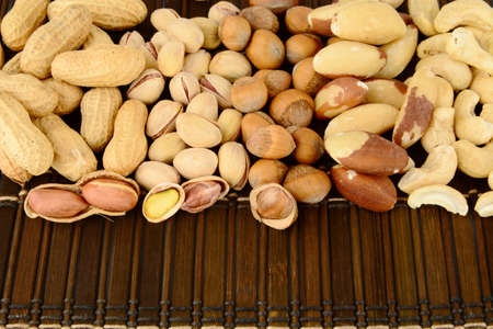 mat like: Many nuts like peanuts,walnuts,pistachios,cashew nuts and brasil nuts, snacks in group on brown mat