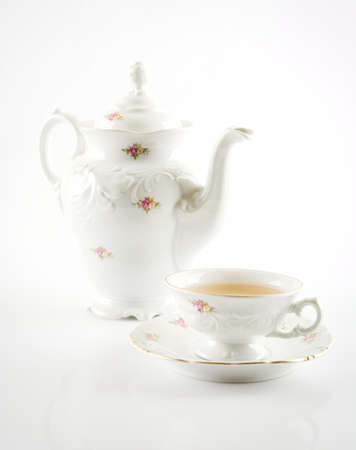 oldstyle: Old-style porcelain jug with tea with a cup of tea on white background retro