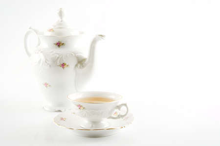 oldstyle: Old-style porcelain jug with tea with a cup of tea on white background