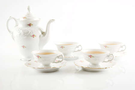 oldstyle: Old-style porcelain jug with four cups of tea on white background Stock Photo