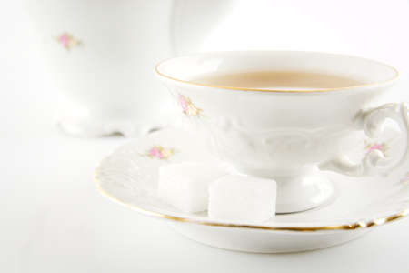 oldstyle: Cropped shot of old-style porcelain jug with a cup of tea on white background Stock Photo