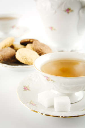 Old-style porcelain kettle with two cups of tea on white background with cookies retro style photo