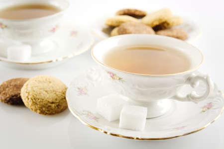 Old-style porcelain cup of tea with cookies on white background photo