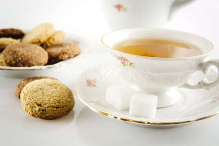 oldstyle: Old-style porcelain kettle with cup of tea with cookies foreground on white background