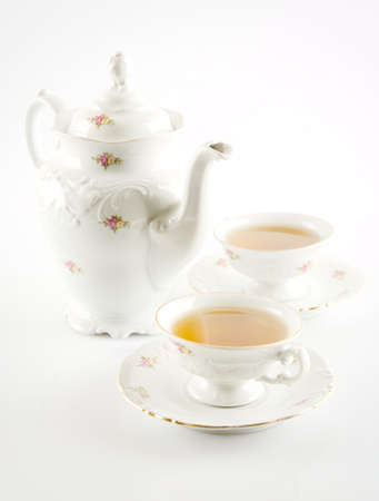 oldstyle: Old-style porcelain kettle with two cups of tea on white background