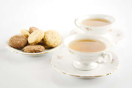 oldstyle: Old-style porcelain cup of tea with cookies on white background