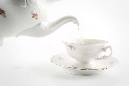 oldstyle: Old-style porcelain pouring tea from jug to cup of tea on white background