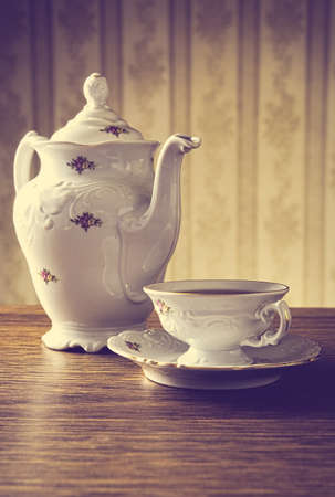oldfashioned: Old-fashioned porcelain jug with a cup of tea with old-fashioned wallpaper background