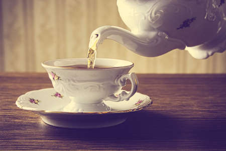 oldstyle: Old-style porcelain kettle pouring tea from jug to cup of tea on wallpaper background