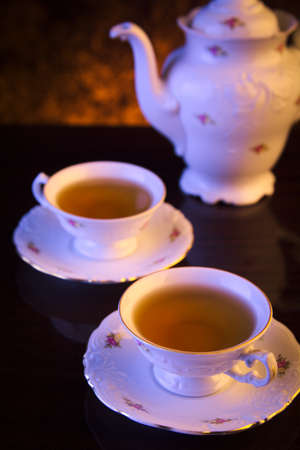 oldstyle: Old-style porcelain jug with two cups of tea on black background