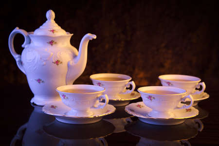 oldstyle: Old-style porcelain jug with four cups of tea on black background