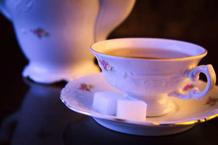 oldstyle: Old-style porcelain jug with cup of tea on black background