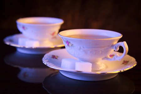 oldstyle: Old-style image with two porcelain cups of tea on black background